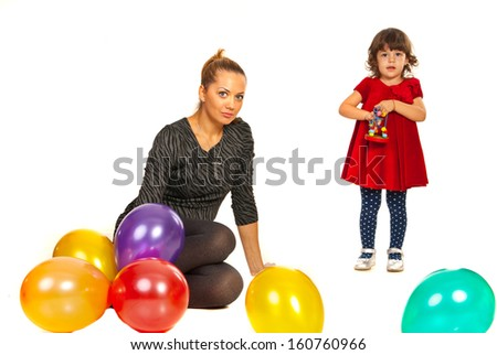 Mother sitting on floor with balloons while her daughter playing with toy at party - stock photo