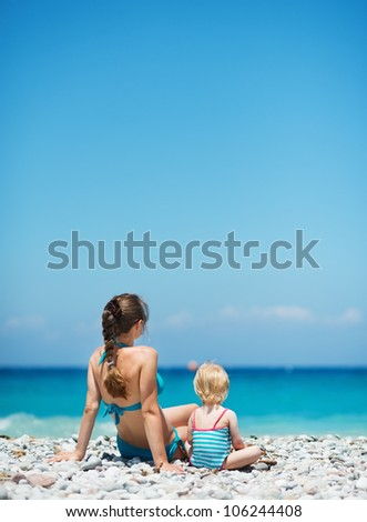 Mother sitting with baby on beach looking into distance. Rear view