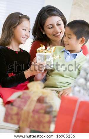 Mother Sitting With Her Son And Daughter, Exchanging Christmas Gifts