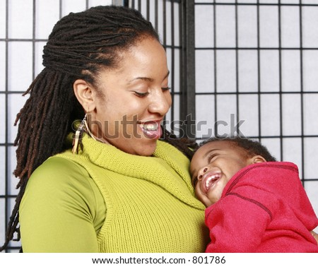 Mother smiling at her laughing baby - stock photo
