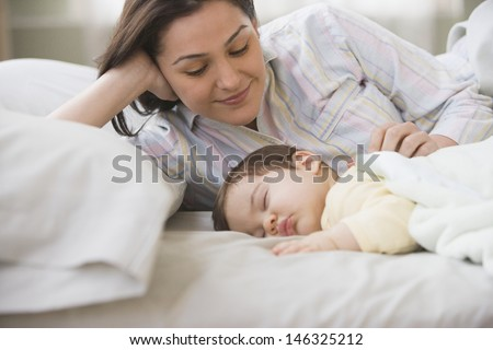 Mother smiling at sleeping baby