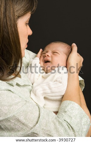 Mother smiling holding baby against black background. - stock photo