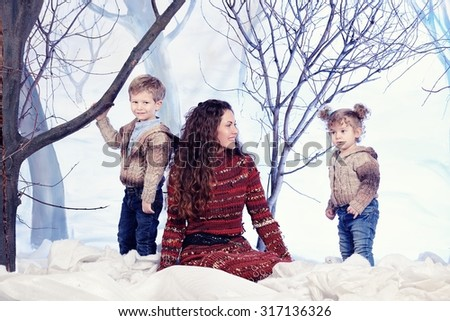 Mother, son and daughter on studio snow forest background - stock photo