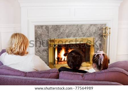 Mother son and daughter sit on the sofa  to read by the fire - stock photo