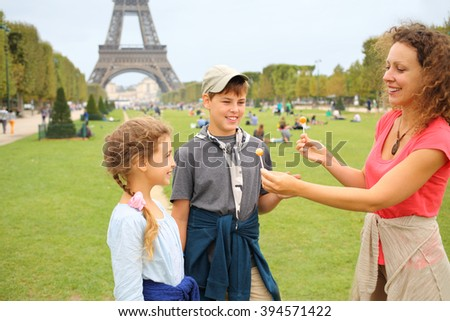 Mother, son and daughter with lollipops near in Paris - stock photo