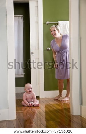Mother standing beside happy baby sitting on wood floor - stock photo