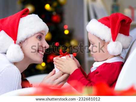 Mother surprising her daughter with christmas gift - stock photo