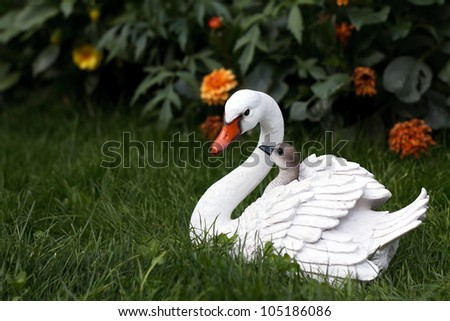 Mother swan with cygnets figurine on the green grass - stock photo