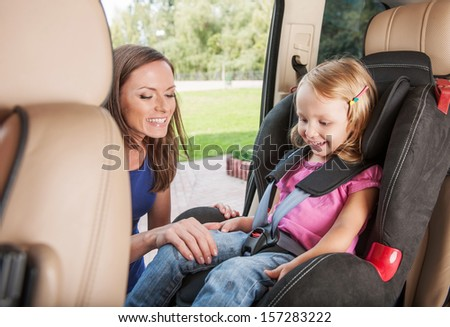 Mother takes care about her daughter in a car, helps her and cheers up - stock photo