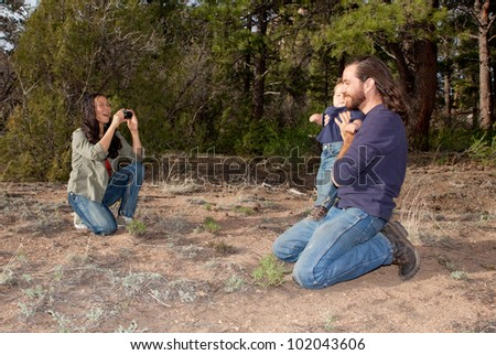 Mother taking a picture of father and son outdoors in nature - stock photo