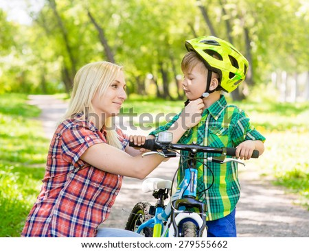 mother taking care of her son, wearing his bicycle helmet - stock photo