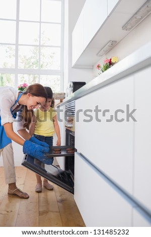 Mother taking cookies out of the oven in the kitchen - stock photo