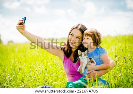 Mother taking photo with her smart-phone camera of herself, her girl and kitten - outdoor in nature - stock photo