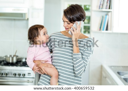 Mother talking on smartphone with daughter in kitchen at home - stock photo