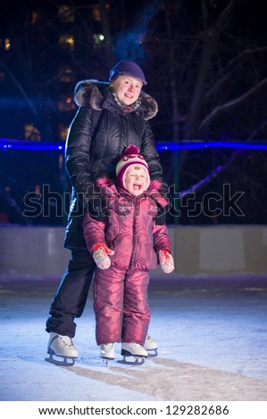 Mother teach adorable girl in skates stay on ice rink in evening