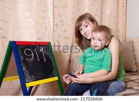 Mother teaches child to emergency phone numbers - stock photo