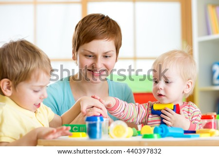 mother teaches children to work with colorful play clay toys - stock photo
