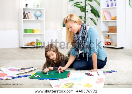 Mother teaches daughter writing while sitting on the carpet in the living room - stock photo