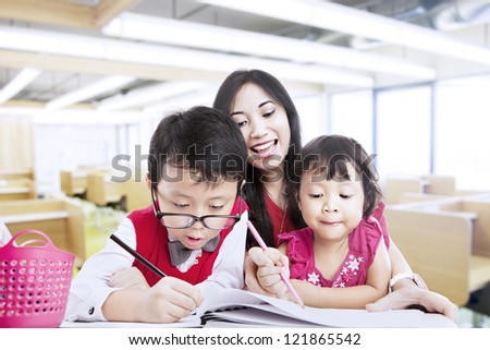 Mother teaches her children to be creative in drawings - stock photo