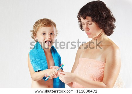 Mother teaches her little cute son to brush their teeth on a white background - stock photo
