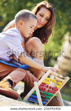Mother teaches her son mathematics in the park - stock photo