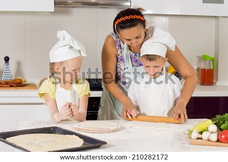 Mother Teaches How to Make Pizza to Kids Wearing Chefs Attire at the Kitchen - stock photo