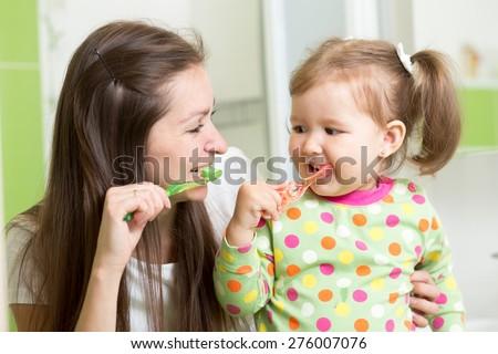 mother teaching daughter child teeth brushing in bathroom - stock photo