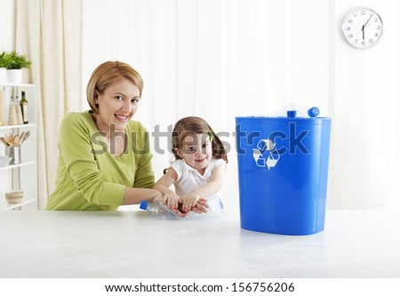 Mother teaching daughter responsibility for recycling  - stock photo