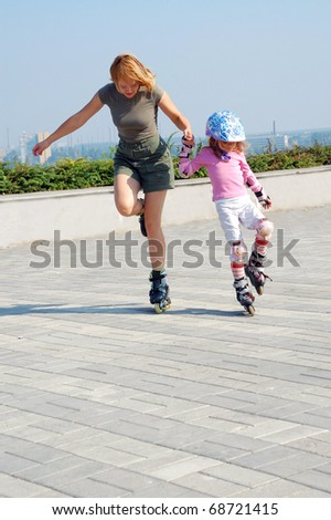 mother teaching daughter rollerblade skating in the park - stock photo