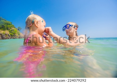 Mother teaching daughter snorkeling near beach on tropical island - stock photo