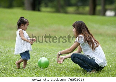 Mother teaching daughter to soccer/ball in the park happily. - stock photo