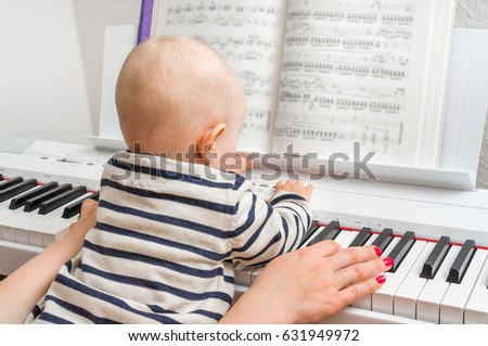 Mother teaching her cute baby to play piano at home