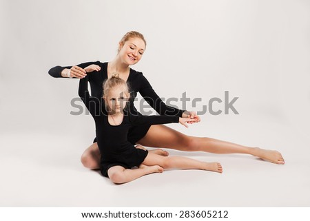 Mother teaching her daughter dancing. mother and daughter are gymnastics. on white background - stock photo
