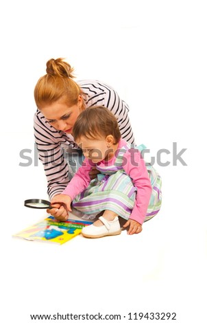 Mother teaching her daughter to read and holding magnifier isolated on white background - stock photo