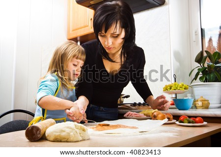 Mother teaching her little daughter how to cook pizza - stock photo