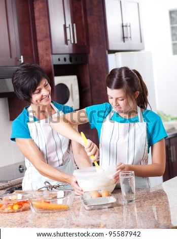 mother teaching teen daughter baking in kitchen - stock photo