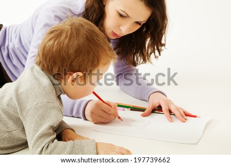 Mother teaching to draw small boy  - stock photo