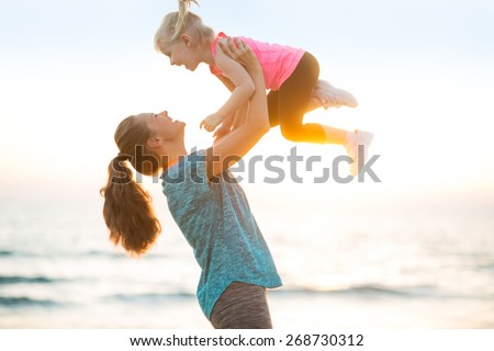 Mother throwing baby up on beach in the evening - stock photo