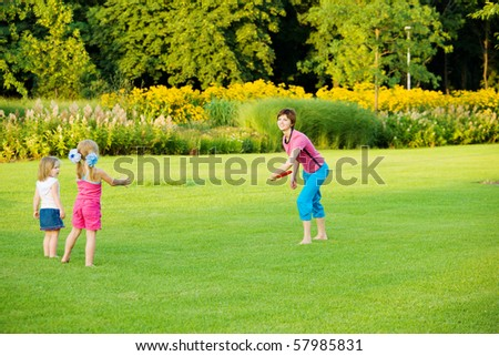 Mother throwing frisbee and kids catching it - stock photo