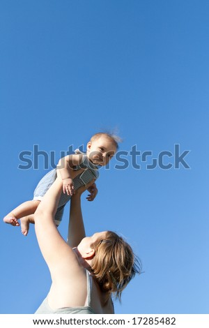Mother throwing up her baby girl against blue sky - stock photo