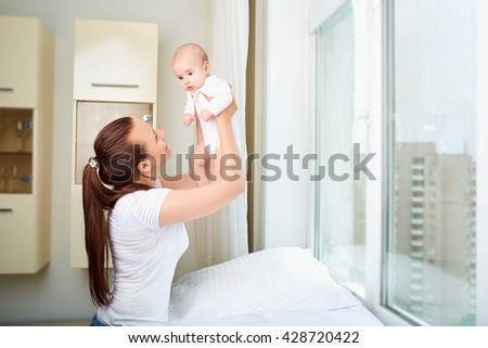 Mother throws up baby, playing at home. - stock photo