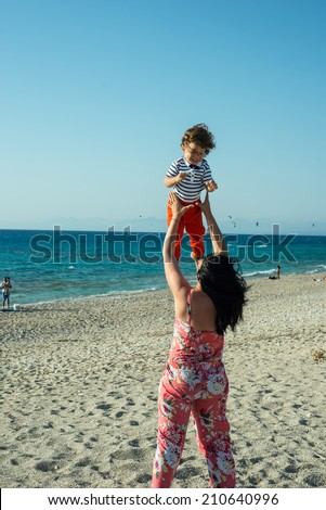 Mother thrwo up to the sky his toddler son at sea  on the beach in the strong wind - stock photo