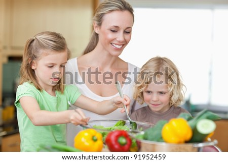 Mother together with daughter and son preparing salad together