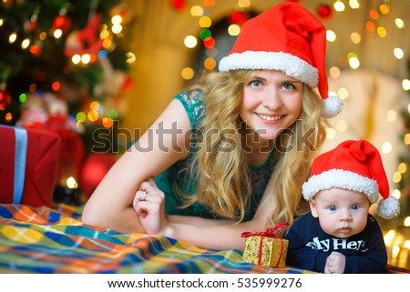 Mother together with the little son lie on a floor in Santa Claus's caps, look in the camera and smile. On a background a set of bright fires. Waiting for a holiday