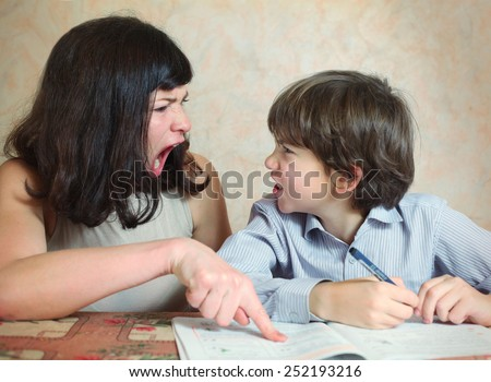 mother try to help her son to do difficult task exercise and quarrel - stock photo