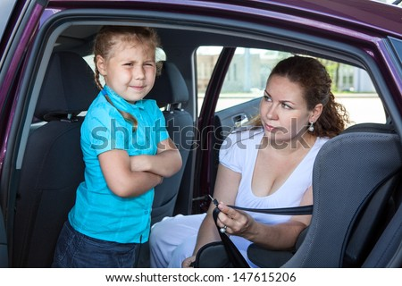 Mother trying to ask a girl get in child safety seat against the wishes - stock photo