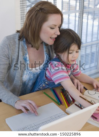 Mother using laptop while daughter coloring book at table in house - stock photo