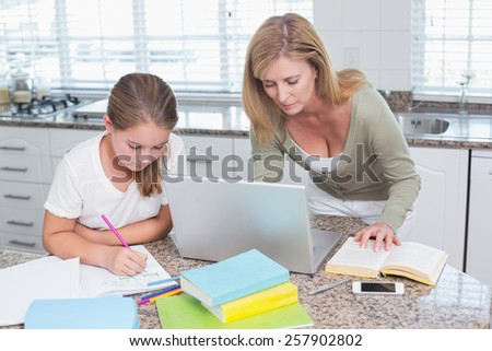 Mother using laptop while daughter doing homework at home in the kitchen - stock photo