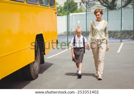 Mother walking her daughter to school bus outside the elementary school - stock photo