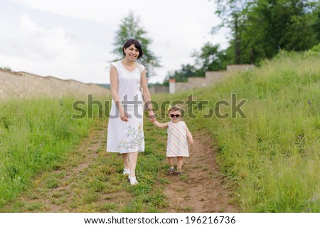 mother walking with her daughter in sunglasses - stock photo